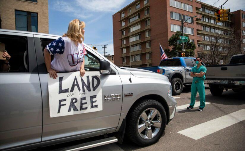 Teilnehmerin eines rechten Autokorsos gegen die Covid-19-Maßnahmen in den USA wird von einem Gesundheits-Arbeiter konfrontiert und am Weiterfahren gehindert